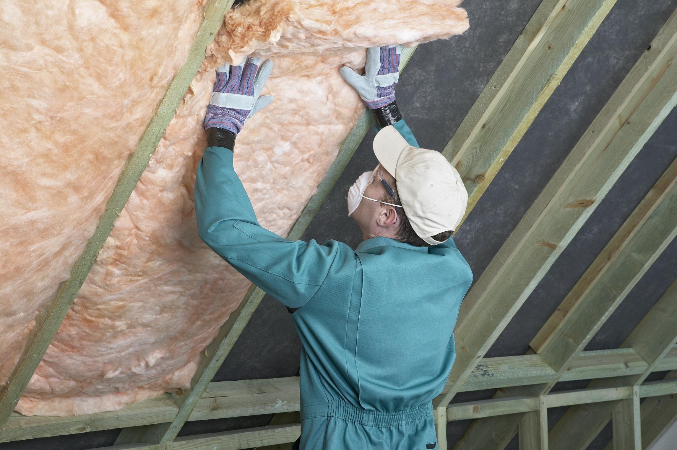 Mężczyzna ocieplający poddasze dachu skośnego, domu jednorodzinnego