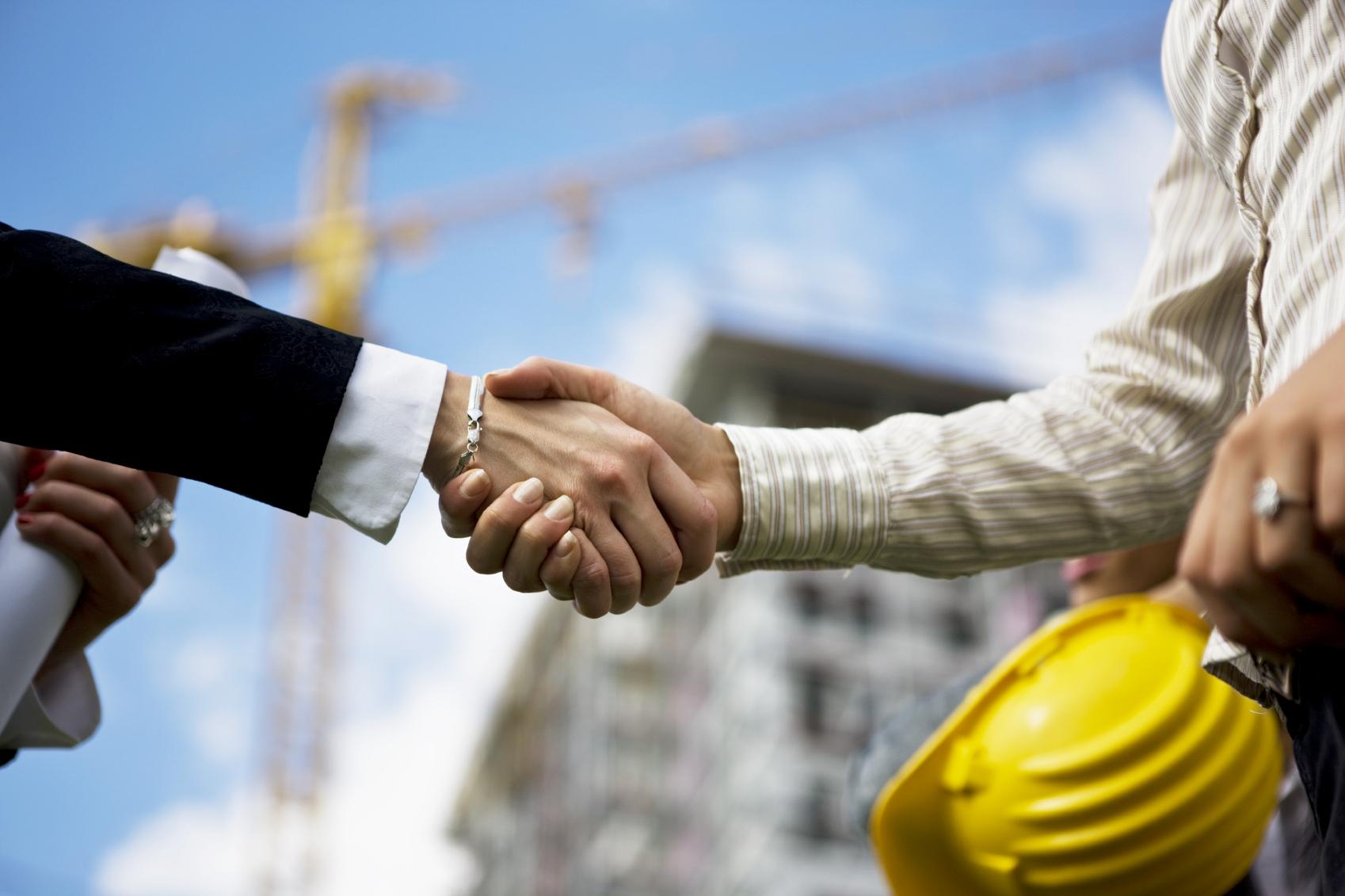 Inwestor i inżynier budowlany podający sobie rękę