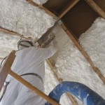Mężczyzna ocieplający poddasze pianką poliuretanową, metodą natrysku piany.