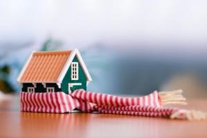 Miniatura domu owinięta szalikiem jako symbol ocieplania domu